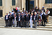 Tour group photo of carnival organisers on steps of Auberge de Castille palace in city centre of Valletta, Malta
