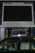 A taxi in front of the darkened screen of the famous Studio Alta in Shinjuku due to power saving measures  after a magnitude 9 earthquake and large tsunami hit the Tohoku region of north east Japan  on March 11th killing nearly 20,000 people and causing massive destruction along the whole coast, and a melt-down at the Fukushima Daichi nuclear power station. Shinjuku, Tokyo, Japan march 16th 2011
