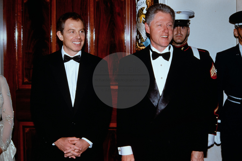 U.S. President Bill Clinton, right, stands with British Prime Minister Tony Blair as they wait to welcome guests in the receiving line during the State Dinner at the White House February 5, 1998 in Washington, DC.