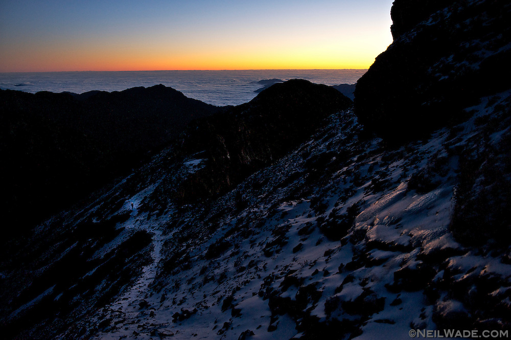 Hiking to the peak of Snow Mountain mean a few hours walking in the predawn darkness.  Here, a hiker walks through the cirque nearing the peak in the dark just before sunrise.