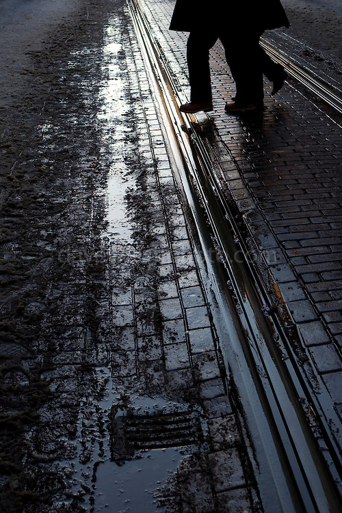 """Man crosses muddy tram rails on Leidsestraat, Amsterdam, December 2010 This mage can be licensed via Millennium Images. Contact me for more details, or email mail@milim.com For prints, contact me, or click """"add to cart"""" to some standard print options."""