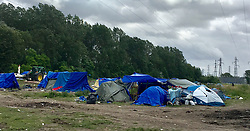 30July2021. Calais, France.<br /> Tents covered with tarps and other makeshift migrant housing inside the migrant refugee camp in Dunkerque. British founded charity Care4Calais along with other aid organisations offer food, assistance, phone charging, haircuts, clothing, tents and more to migrant refugees. A new 'Jungle' appears to be springing up from the trees and woods on the outskirts of Dunkerque where conditions are not as hostile or inhospitable as they are currently in Calais 30km to the south.<br /> Photo©; Charlie Varley/varleypix.com