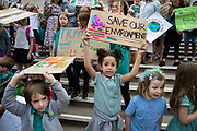 London Borough of Hackney, London. May 24th . Third strike by school students. Hackney primary school pupils went to the Town Hall after school to protest about the climate emergency. A young girl in school uniform holds a placard saying Save our environment.