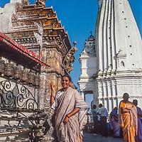 A Hindu woman walks bast Tibetan Buddhist prayer wheels at Swayambhu Temple in Kathamandu, Nepal, 1986.