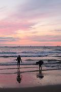 Spelende kinderen aan de zee met zonsondergang, vrachtboten op de achtergrond, Den Haag - Playing children at the sea during sunset, cargo-boats on the background, The Hague, Netherlands