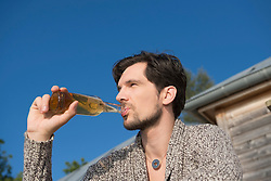 Portrait young man drinking beer close up
