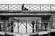 Belgie, maas, 20-6-1987Reisreportage voor een reisnummer van Intermediair van een tocht over de Maas in een klein motorjachtje, van Maasbracht in Nederland tot aan Charleville-Mezieres in N.- Frankrijk. Sluisjes die handmatig bediend werden, maar ook een bij Ternaaien met een hoogteverschil van 12 meter.. Het was een reportage van 'slow journalism'. Varend op de rivier verandert het besef van tijd en snelheid. Een handmatig bediende sluis . Een man met houten kruiwagen loopt over de brug .Foto: Flip Franssen