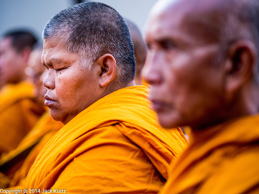 23 NOVEMBER 2014 - BANGKOK, THAILAND: A Buddhist monk prays during a mass alms giving ceremony in Bangkok Sunday. 10,000 Buddhist monks participated in the ceremony on Rajadamri Road in front of Central World shopping mall. The alms giving was to assist Buddhist temples in the insurgency wracked southern provinces of Thailand, where Buddhist monks on their alms rounds have been targeted by Muslim extremists. The ceremony was sponsored by Wat Phra Dhammakaya, the center of the Dhammakaya Movement, a Buddhist sect founded in the 1970s. The temple has become active in Thai politics.    PHOTO BY JACK KURTZ
