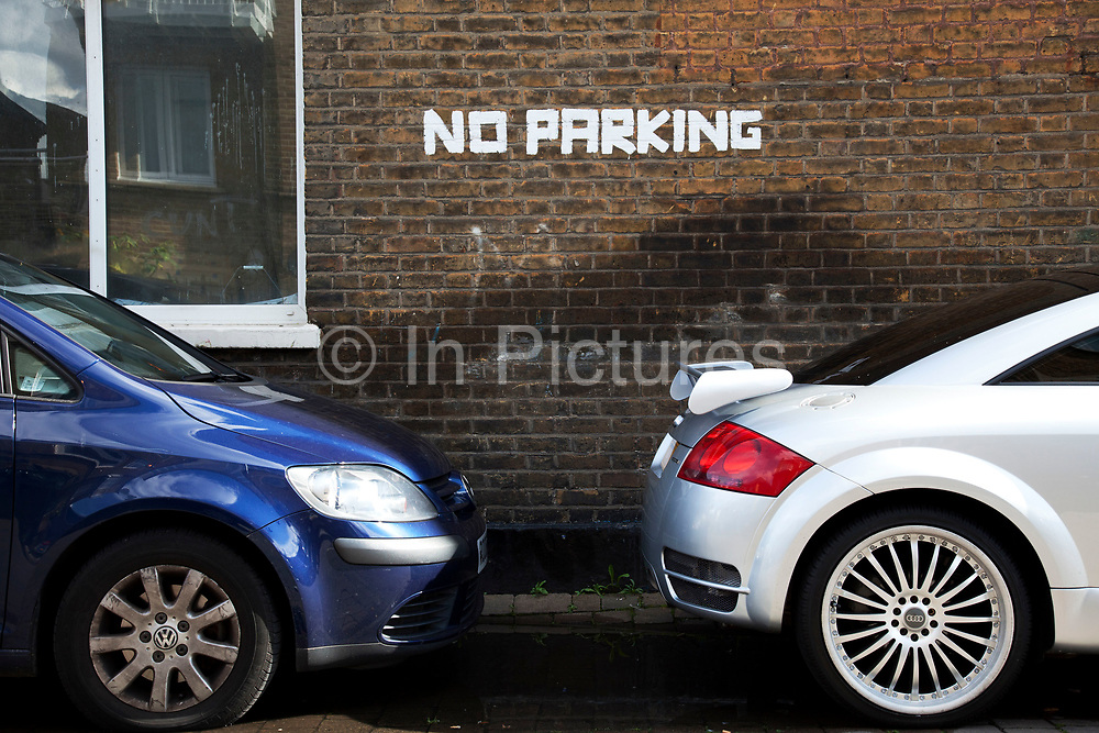 Cars parked right in front of a hand painted No Parking sign on a brick wall in a residential street in London.