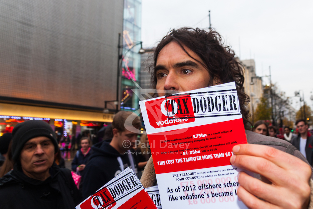 """Oxford Street, London, December 5th 2014. Actor and Comdeian turned political activist Russel Brand visits several big brands'  stores including Boots, Apple and Vodafone in London accusing them of dodging tax whilst those most in need of benefits are facing cuts and increased hardship. A leaflet being distributed by him claims £14 billion is lost every year, through tax avoidance and loopholes exploited by big business. PICTURED: Comedian Russel Brand distributes leaflets accusing Vodafone of deing a """"Tax Dodger""""."""