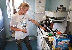 © Licensed to London News Pictures. 11/08/2017. London, UK. Tyrone Thomas checks the heat on his new electric  cooking hotplate in his 9th floor flat. The hotplate was provided by the council after the gas was turned off. Residents on the Ledbury Estate in south London have been told they will have to leave their properties over the next few weeks. A structural survey carried out after the Grenfell fire found cracks that could lead to a collapse of the building if a gas explosion occured in one of the flats. Photo credit: Peter Macdiarmid/LNP