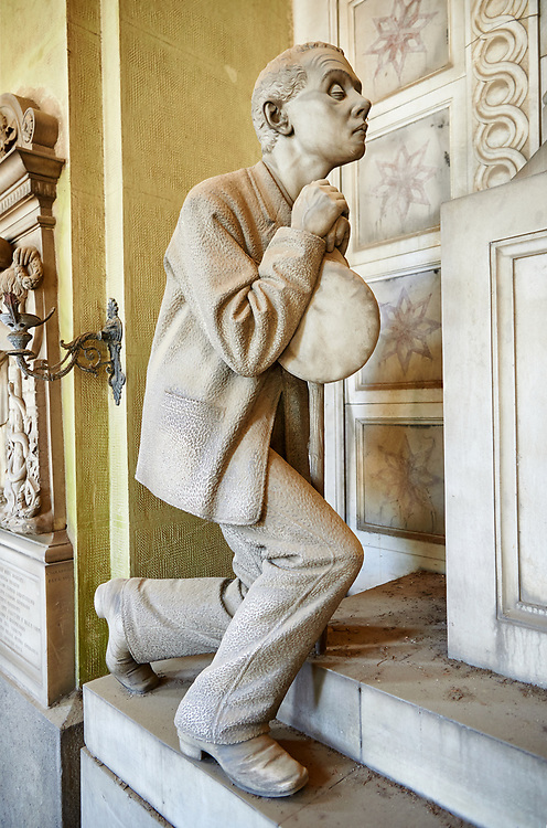 Picture and image of the Realistic blind man stone funary monument sculpture commissioned by Enrico Amerigo for his sisters memory. beside the pedestal on which the sculptor set the deceased's bust he placed, on the left, the figure of an old blind man, kneeling down and leaning on a stick; on the right he placed the figure of a young orphan girl, recognizable as such by her kindergarten uniform, portrayed in the act of making the sign of the cross. This work belongs to the Realism, a trend which was typical during the 1880s and 1890s, according to which the orphans, the poor, the sick and all those who benefited from somebody's generosity had to be portrayed in a concrete fashion. Sculptor G Moreno 1890. Section A, no 53, The Staglieno Monumental Cemetery, Genoa, Italy .<br /> <br /> Visit our ITALY PHOTO COLLECTION for more   photos of Italy to download or buy as prints https://funkystock.photoshelter.com/gallery-collection/2b-Pictures-Images-of-Italy-Photos-of-Italian-Historic-Landmark-Sites/C0000qxA2zGFjd_k<br /> If you prefer to buy from our ALAMY PHOTO LIBRARY  Collection visit : https://www.alamy.com/portfolio/paul-williams-funkystock/camposanto-di-staglieno-cemetery-genoa.html
