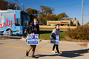28 OCTOBER 2020 - DES MOINES, IOWA: Drake University students walk away from a Get Out the Vote event with Biden/Harris campaign signs. Rep. Axne hosted a Get Out the Vote event at Drake University Wednesday morning. Axne, a Democrat, represents Iowa's 3rd District, from the southwest corner of the state up through the Des Moines area. She is in a tight race for reelection with David Young, the Republican she defeated in 2018.    PHOTO BY JACK KURTZ