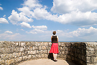 Female leaning against castle wall on sunny summer day, Germany