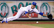 Kansas City Royals third baseman Jamey Carroll dives for a ground ball hit by Miami Marlins' Donovan Solano in the fourth inning of a baseball game at Kauffman Stadium in Kansas City, Mo., Tuesday, Aug. 13, 2013. Carroll was able to make the catch, and the throw for an out. (AP Photo/Colin E. Braley)