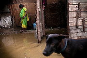 A pregnant woman is moving around inside her flooded home in the impoverished Oriya Basti colony in Bhopal, Madhya Pradesh, India, near the abandoned Union Carbide (now DOW Chemical) industrial complex.