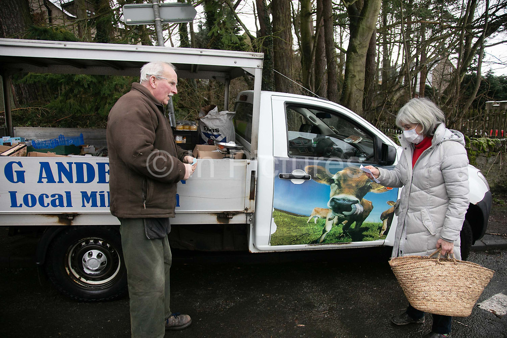 The milkman Gordon Anderson takes an order from a local resident on 7th of January 2021 in Stow, Scottish Borders, United Kingdom. Gordon Anderson runs a fresh milk and vegetables delivery service with his wife and they deliver to local houses and farms in and around the village of Stow. Twice a week he sets up shop out of his van in the village for an hour while he restock from his small warehouse in the village center.
