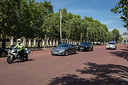 On the day that Britains new Conservative Party Prime Minister, Boris Johnson enters Downing Street to begin his government administration, replacing Theresa May after her failed Brexit negotiations with the European Union in Brussels, Johnsons car and police escort speeds down the Mall en-route to Buckingham Palace to seek the Queens permission to form a new government, on 24th July 2019, in Westminster, London, England.