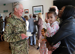 The Prince of Wales, Colonel Welsh Guards, meets Starr Mitchell, 2 and her mother Lisa Mitchell, the family of Guarsdman Craig Mitchell of the 1st Battalion Welsh Guards, following their return from Afghanistan, at Elizabeth Barracks, Pirbright Camp in Woking.