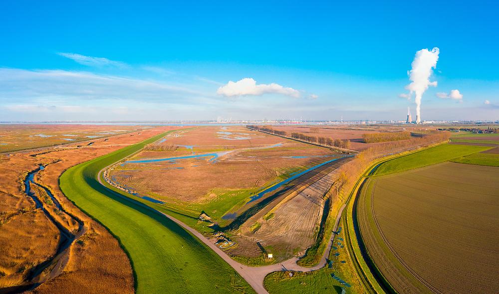 Nederland, Zeeuws-Vlaanderen, Nieuw Namen, 05–11-2020; Hertogin Hedwigepolder met Verdronken Land van Saeftinghe (links), gezien naar de Westerschelde en haven Antwerpen met de kerncentrale van Doel. In verband met de verdieping van de vaargeul van de nabijgelegen Westerschelde moet er volgens de Europese habitatrichtlijn natuurcompensatie komen. Door de polder te ontpolderen wordt er grond terug gegeven aan de natuur, zogenaamde natuurcompensatie. De ontpoldering zal plaats vinden in 2021, bestaanden boerderijen zijn reeds gesloopt evenals wegen.<br /> De maatregelen zijn omstreden, in het Belgisch deel van het gebied,  Belgische Prosperpolder, aan de andere kant van de grens, is men reeds begonnen.<br /> Hertogin Hedwigepolder with Drowned Land of Saeftinghe (left). Because of the future enlargement of the fairway of the nearby Westerschelde, the nature has to be compensated (according to the European Habitats Directive). The Hertogin Hedwige polder (and the adjacent Belgian polder - on the other side of the border - the Prosperpolder) are to be given back to nature, i.e. are to be 'de-polderd'. The measures are controversial, but in the Belgian part of the polders works have already been started.<br /> drone-opname (luchtopname, toeslag op standaard tarieven);<br /> drone recording (aerial, additional fee required);<br /> copyright foto/photo Siebe Swart