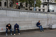 Three men use their phones and a laptop beneath the slogan Live Simply and Live in Peace has been written on a wall by an environmental activist protesting about Climate Change during an occupation of Trafalgar Square in central London, the third day of a two-week prolonged worldwide protest by members of Extinction Rebellion, on 9th October 2019, in London, England.