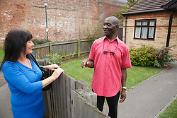 Elderly black man greeting white woman carer at gate