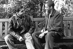 Teenager sitting on park bench talking to older man; smiling,