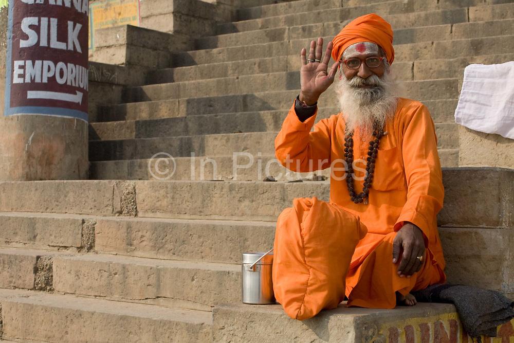 Sadhu babba in orange robes waving on the banks of the Ganges, Varanasi, Uttar Pradesh, India. .