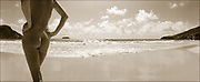 Sepia panoramic photo of nude woman standing on beach with hands on hips. The beach is Grand Anse de Saline in Saint Barthelemy, FWI