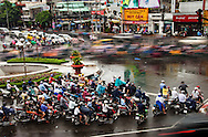The motorbike is Vietnam's favored mode of transportation, having replaced the bicycle. Here traffic moves in a blur as thousands of motorbikes pass through the busy Saigon intersection every hour. Robert Dodge, a Washington DC photographer and writer, has been working on his Vietnam 40 Years Later project since 2005. The project has taken him throughout Vietnam, including Hanoi, Ho Chi Minh City (Saigon), Nha Trang, Mue Nie, Phan Thiet, the Mekong, Sapa, Ninh Binh and the Perfume Pagoda. His images capture scenes and people from women in conical hats planting rice along the Red River in the north to men and women working in the floating markets on the Mekong River and its tributaries. Robert's project also captures the traditions of ancient Asia in the rural markets, Buddhist Monasteries and the celebrations around Tet, the Lunar New Year. Also to be found are images of the emerging modern Vietnam, such as young people eating and drinking and embracing the fashions and music of the West. His book. Vietnam 40 Years Later, was published March 2014 by Damiani Editore of Italy.