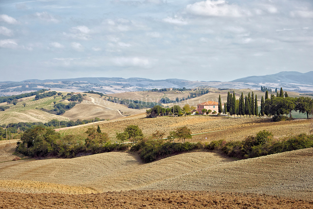Image of an inviting pink Tuscan villa in Val d'Orcia, Italy.