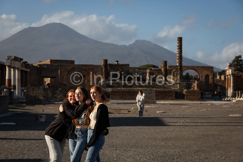 Three young women tourists pose for a photograph in the nearly-deserted Forum at the Pompeii Archeological Park on Friday 6th March 2020 in Pompei, Italy. Park officials estimate that visitor numbers are down to a sixth of what they would normally be as a result of the spread of Coronavirus, which has prompted the closure of all Italian schools and universities, and the postponing of many sporting events. .