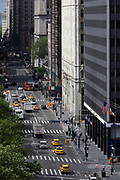 Seen from the roof of a Federal building, an aerial view of Broadway in New York City. The straightness of the road with traffic consisting of yellow taxi cabs, trucks and tour buses make their way southwards in Lower Manhattan. The Stars and Stripes flag is seen hanging on the side of a skyscraper and pedestrians walk along pavements (sidewalks) on the right. The lighter shade building in the middle is the Woolworth Building whose address is 233 Broadway. Broadway was originally the Wickquasgeck Trail, carved into the brush of Manhattan by its Native American inhabitants. This trail originally snaked through swamps and rocks along the length of Manhattan Island. The road now runs 13 mi (21 km) through Manhattan and 2 mi (3.2 km) through the Bronx, exiting north from the city to run an additional 18 mi (29 km) through other municipalities.