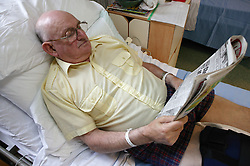 Patient relaxing and reading newspaper on orthopaedic Ward after knee operation,
