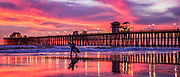 Surfer Walking On The Beach During A Low Tide And Sunset At The Oceanside Pier