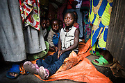Displaced children sit on a tarp among their parents in the house where they sleep in Goma, Eastern Democratic of Congo on Monday December 15, 2008. Justine Faida, who lives in the house with her husband and four children, decided to take in 20 people from Rutshuru, about 70km north of Goma, after they reached the provincial capital, running away from conflict.