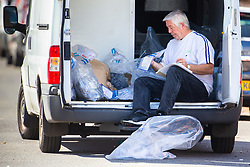 An investigator goes through bags of evidence recovered from the house where seven-year-old Joel Urhie died in a suspected arson attack on his home in Deptford in the early hours of Tuesday 7th August. London, August 08 2018.