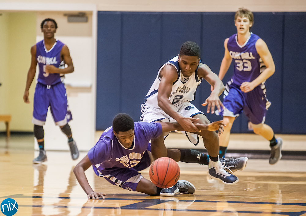 Cox Mill's Gianni Smith (23) and Hickory Ridge's Kyle Meertins chase down a loose ball Tuesday night at Hickory Ridge High School. Cox Mill won the game 68-65.