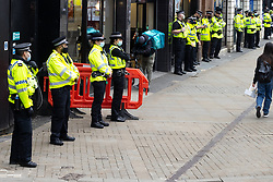© Licensed to London News Pictures. 20/03/2021. Manchester, UK. Police stand back and watch as anti lockdown , anti mask , pro Christiantiy , Kill the Bill and Reclaim the Streets protesters congregate and demonstrate in Piccadilly Gardens in Manchester City Centre . There is opposition to the Police, Crime, Sentencing and Courts Bill 2021 that is currently before Parliament and anger after the death of Sarah Everard in London . Photo credit: Joel Goodman/LNP