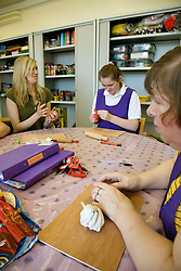 Day Service Assistant working with a Group of Day Service users with learning disabilities in an arts and crafts session,