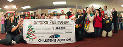 A record breaking $165, 300 was raised by Patrick's Pub Mania for the annual Children's Christmas Auction, helping to propel the auction to a record $415,500.  (Alan MacRae/for the Laconia Daily Sun)