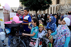 (170729) -- ALEPPO (SYRIA), July 29, 2017 (Xinhua) -- Children line up for fairy floss near the historic citadel of Aleppo city in northern Syria on July 28, 2017. The rebels had stayed in the east of Aleppo for five years before they evacuated in December of 2016. Seven months after the Syrian army took full control over the city, life starts to beat again through devastation and destruction in the area. (Xinhua/Ammar Safarjalani) (zjy) (Photo by Xinhua/Sipa USA)