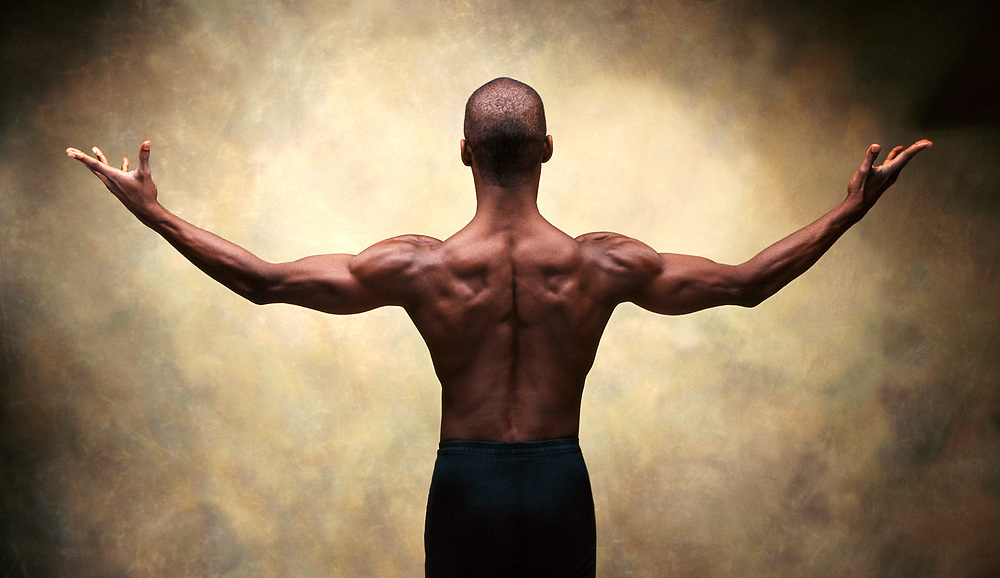 A studio shot of the back of a male dancer in studio.