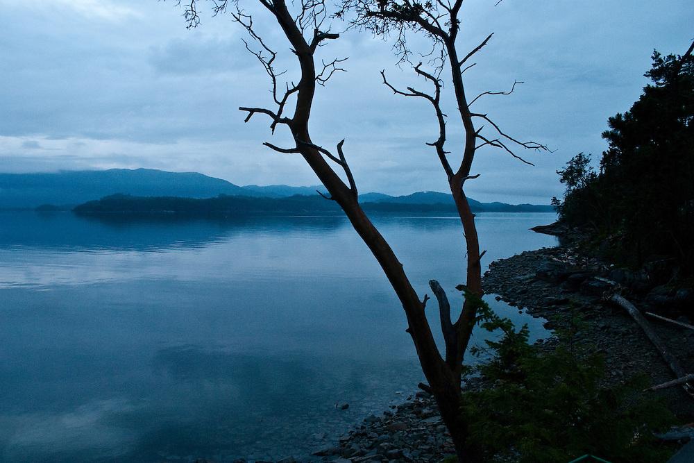Dawn breaks over a blue grey sky above Malaspina Strait, Sunshine Coast BC