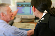 A female prison officer helps an inmate from the Vulnerable Prisoners Unit with his computer work. HMP Wandsworth, London, United Kingdom