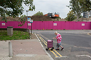 An elderly lady walks slowly with her shopping trolley across a road on the Aylesbury Estate, on 4th September 2018, in Southwark, London, England. The Aylesbury Estate contained 2,704 dwellings in approximately 7500 residents and built between 1963 and 1977 and for decades it was seen as a symbol of the failure of British social housing. There were major problems with the physical buildings on the estate and the poor perception of estates in Britain as a whole have led to the Aylesbury Estate gaining the title of one of the most notorious estates in the United Kingdom. Demolition is in progress for the regeneration of the Aylesbury Estate to consist of 3,500 new homes, 50% of which, according to Southwark council, will be affordable.