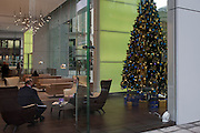 Businessmen meet in the Aviva office foyer in front of a Christmas tree at the insurance corporate's HQ, on 9th December 2016, in the City of London.