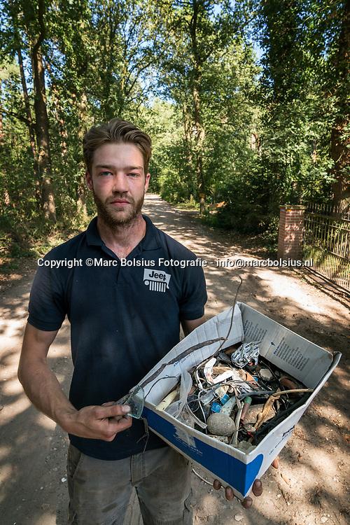 Nederland,  Vught, Joel van Boxtel met het groffe puin dat glas,spijkers,kapotte tegels en asbest bevat. De Gemeente heeft op deze manier het pad verhard.
