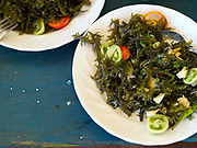 A typical seaweed dish - firstly the seaweed is boiled then tomatoes, onion and vinegar are added, Tamiao, Bantayan Island, The Philippines. Before Typhoon Haiyan, Bantayan Island was the largest seaweed producer in Cebu province. The typhoon destroyed seaweed farms leaving over 2000 farmers without essential equipment and seedlings. Oxfam awarded cash grants to around 700 families to finance the purchase of seaweed seedlings and farming equipment including ropes, poles and floaters.