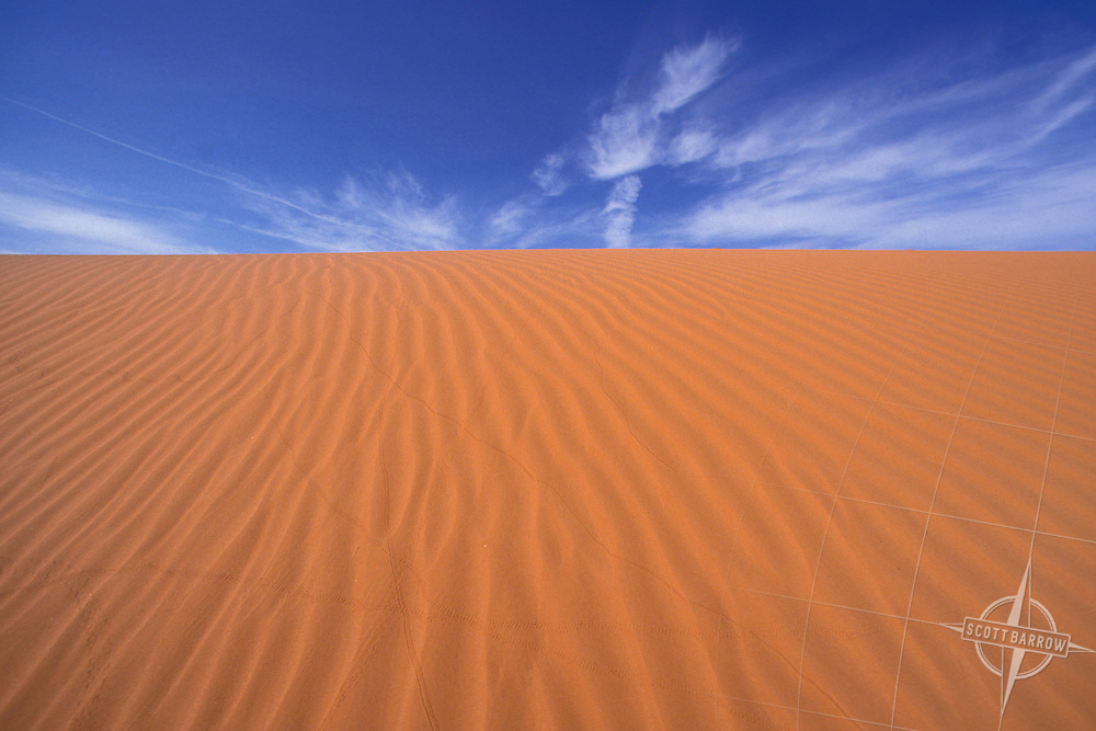 Wind sculpted sand dune horizon with blue sky.